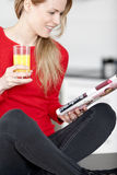 Young woman reading a magazine at home Royalty Free Stock Photography