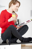 Young woman reading a magazine at home Stock Photo