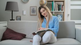 Young woman reading magazine at home. Charming girl flipping a fashion magazine pages while sitting on the couch in the stock video footage