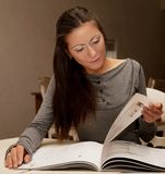 Young  woman reading magazine at home Stock Images