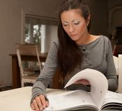 Young  woman reading magazine at home Stock Photography