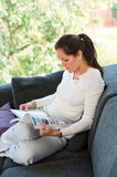 Young woman reading magazine living room couch Royalty Free Stock Image