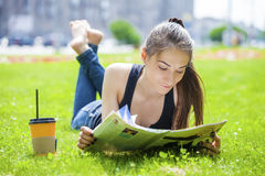 Young woman reading magazine lying on grass royalty free stock images