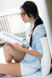 Young woman reading a magazine sitting on the floor Stock Photography