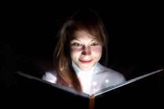 Young woman reading a magic book. Collage of a young woman reading a magic book royalty free stock photos