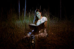 Young woman reading magic book at dark night forest Royalty Free Stock Image