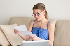 Young woman reading mail letter sitting with laptop on couch. Young woman holding letter sitting near laptop on couch, looking at paper in hands with light smile stock photography
