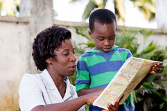 Young woman reading a map with her child. In travel and tourism, a young mother reads a map with her child in the country royalty free stock photo