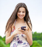 Young woman reading a message on the phone Royalty Free Stock Image