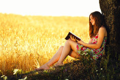 Young woman reading on nature Royalty Free Stock Photos