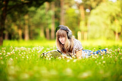 Young woman reading on nature, smiling and listening to the music Royalty Free Stock Photo
