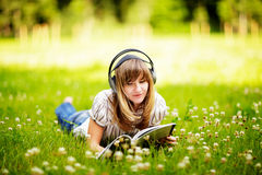 Young woman reading on nature, smiling and listening to the music Royalty Free Stock Image