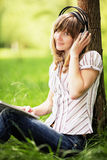 Young woman reading on nature, smiling and listening to the music Stock Photos