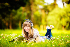 Young woman reading on nature, smiling and listening to the music Stock Image