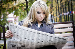 Young woman reading a newspaper Royalty Free Stock Photos
