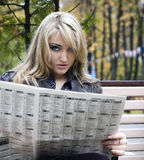 Young woman reading a newspaper Stock Photos