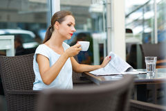 Young woman reading a newspaper and drinking morning coffee in a Stock Photos
