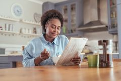 Young woman reading the newspaper while eating breakfast at home. Smiling young African woman sitting at her kitchen table in the morning reading the newspaper stock image