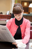 Young woman reading newspaper in hotel lobby Royalty Free Stock Photography