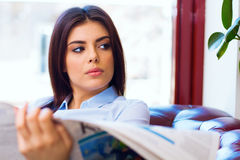 Young woman reading the newspaper at office Royalty Free Stock Photography