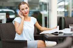 Young woman reading a newspaper and talking on a cell phone sitt Royalty Free Stock Photography