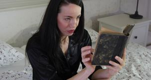Young woman reading old book in bed wearing black dressing gown - face emotions. Young woman reading old book in bed wearing black dressing gown and enjoy the stock video