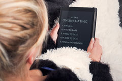 Young woman reading about online dating on tablet Royalty Free Stock Image