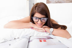 Young woman reading papers lying on the bed Stock Photography