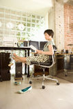 Young woman reading paprerwork in office, barefeet resting on computer Royalty Free Stock Photography
