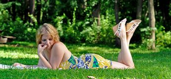Young woman reading in a park Stock Photo