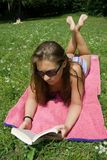 Young woman reading in park. In summer Stock Images