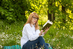 Young woman reading in the park. Young woman with glasses reading a book in the park Stock Image