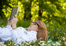Young woman reading in the park. Young woman with glasses lying and reading in the meadow Stock Photo