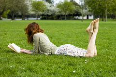 Young woman reading in the park. Young woman lying in the grass and reading in the park on a sunny day Stock Photo