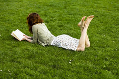 Young woman reading in the park. Young woman lying in the grass and reading in the park on a sunny day Stock Photography