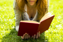 Young woman reading in the park. On a sunny day Royalty Free Stock Photo
