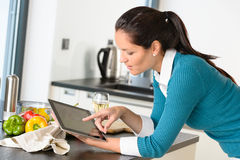 Young woman reading recipe tablet kitchen searching. Young woman reading recipe tablet searching kitchen preparing vegetables Stock Image
