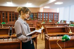 Young woman in reading room, university library. Pretty young woman in reading room, university library. Female person in knowledge depository royalty free stock photo