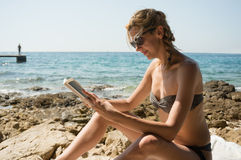 Young woman reading by the sea Royalty Free Stock Photography