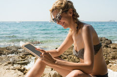 Young woman reading by the sea Stock Photography