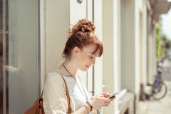 Young woman reading a sms on her mobile Stock Photography