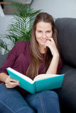 Young  woman reading on the sofa Stock Image