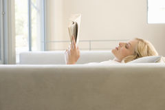 Young woman reading on sofa, profile Royalty Free Stock Photo
