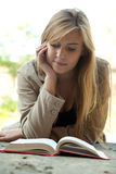 Young woman reading or studying book Stock Images