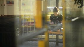 Young woman reading a Tablet or ebook in a train station while is waiting for public transport, through the bus camera stock footage