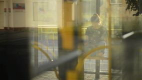 Young woman reading a Tablet or ebook in a train station while is waiting for public transport, through the bus camera stock video footage