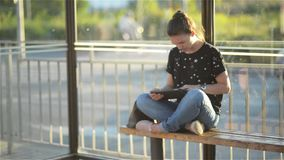 Young woman reading a Tablet or ebook in a train station while is waiting for public transport and looking at the her stock video