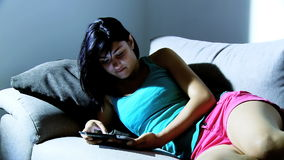 Young woman reading on tablet at home stock footage