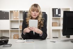 Young woman reading a tablet in the office Royalty Free Stock Image