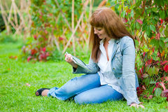 Young woman reading in tablet pc Royalty Free Stock Photos